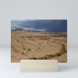 Arroyo (also called a gulch or wash) and distant mesa in a desert landscape scene during a rainstorm in monsoon season in the Chamisa Wilderness Study Area in Sandoval County, New Mexico, USA Mini Art Print