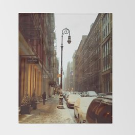 Soho snowing. Winter in New York Throw Blanket