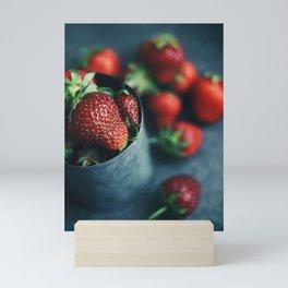 Ripe strawberries scattered around an iron mug Mini Art Print