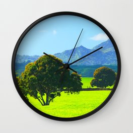 green tree in the green field with green mountain and blue sky background Wall Clock