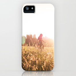 Woman walking through meadow at sunset iPhone Case
