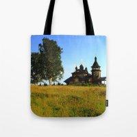 russia Tote Bags featuring Wooden Church, Merkushino, Russia by Svetlana Korneliuk