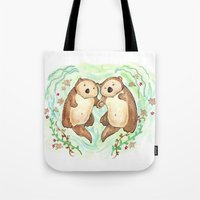 otters Tote Bags featuring Otters Holding Hands by Georgia Dunn