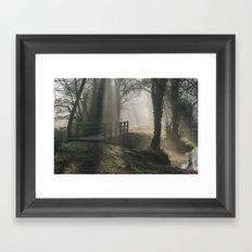 Sunlight through mist and fog over an old wooden footbridge. Norfolk, UK. Framed Art Print