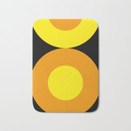 Two suns, one yellow with orange rays,the other orange with yellow rays,both floating in a black sky Bath Mat