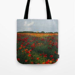 Church and field of red poppies in evening light. Holme Hale, Norfolk, UK Tote Bag