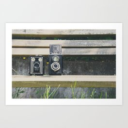 two vintage cameras sitting on a park bench ... Art Print