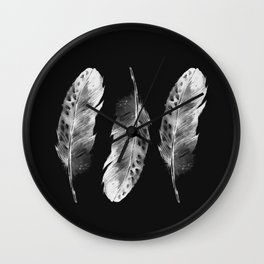 Three feathers on black background Wall Clock