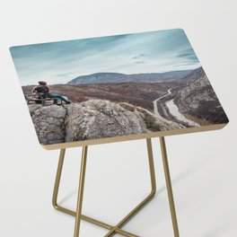 Girl sitting on the bench on the edge of the canyon with amazing view in front of her Side Table