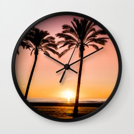 Orange bright sunset at the beach between palms Wall Clock