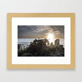 Sunset behinds rocks on a cliff Framed Art Print