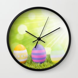Decorated Easter eggs in the grass with a green background Wall Clock