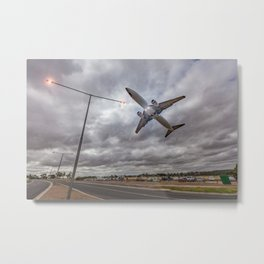 January 2, 2017:  Passenger jet airplane flying low in the sky right above glowing street lights in Metal Print