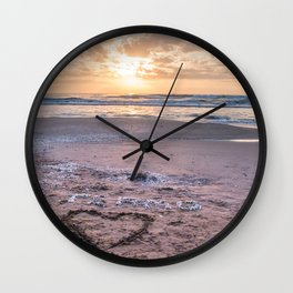 Love note Te Amo with the heart drawing on the beach at sunrise Wall Clock