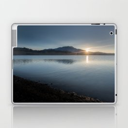 View of the sun rising over the mountaintop from across the lake Laptop & iPad Skin