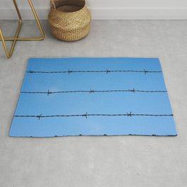 Contseptual shot of barbed wire over blue sky Rug