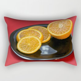Sliced orange on the black plate and red background Rectangular Pillow