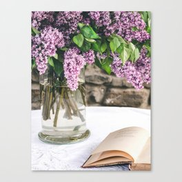 Romantic photo composition with lilac and vintage book on white lace tablecloth. Canvas Print