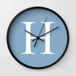 Letter H sign on placid blue color background Wall Clock
