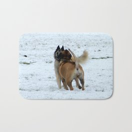 Dogs playing in the snow Bath Mat