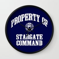 stargate Wall Clocks featuring Property of Stargate Command Athletic Wear White ink by RockatemanDesigns