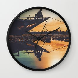 Kid sitting on a boat during the sunset Wall Clock