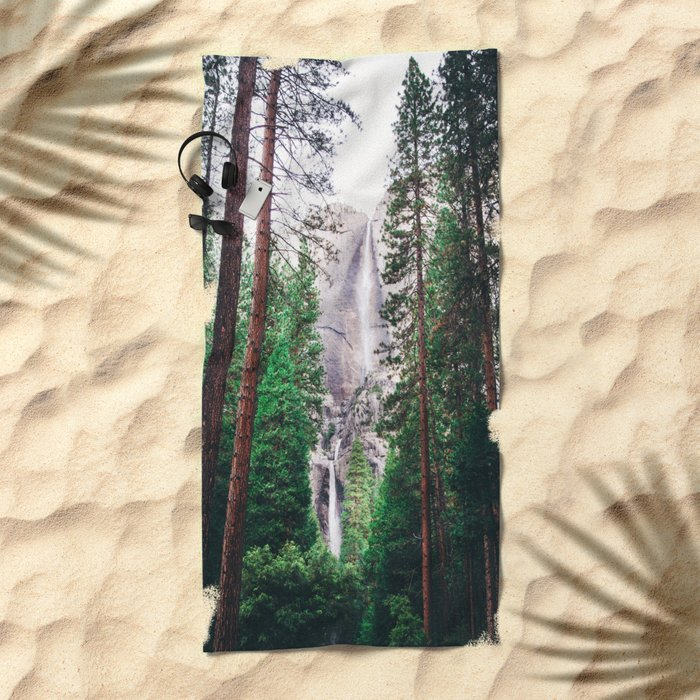 Waterfall amongst trees Beach Towel