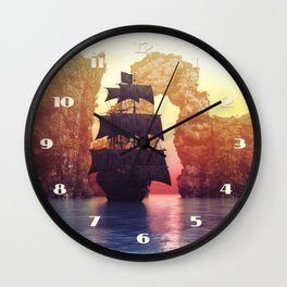 A pirate ship off an island at a sunset Wall Clock