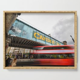 Long exposure of the painted Camden Lock bridge across Camden High Street with a blurred red London Double Decker bus passing beneath it Serving Tray