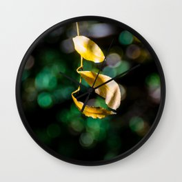 Yellow leaves in colorful bokeh Wall Clock