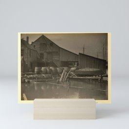 Doris Ulmann  (1882–1934), Weathered buildings on wharf, with barrels in front and masts of ships sh Mini Art Print