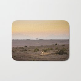 Single lioness relaxes while African sun sets Bath Mat