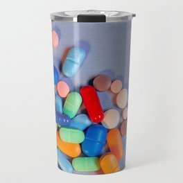 Pills of various colors on a blue neutral background Travel Mug