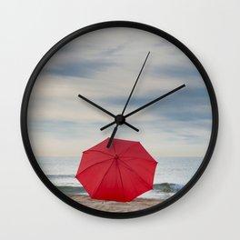 Red umbrella lying at the beach Wall Clock