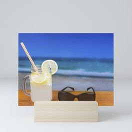 Refreshing Lemon Drink on a Table Against the Sea Mini Art Print