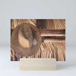 Panama Hat in Palm-Roofed Hut Mini Art Print