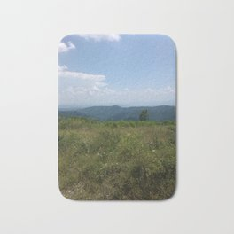 Meadow and mountains in the distance Bath Mat