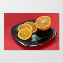 Sliced orange on the black plate and red background Canvas Print