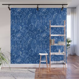 Pattern from women faces on blue background Wall Mural