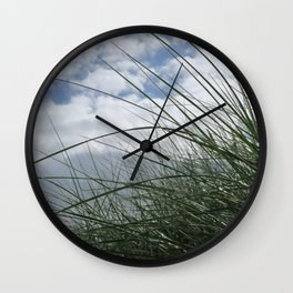 Grass in the dunes at sea against blue sky with white clouds Wall Clock