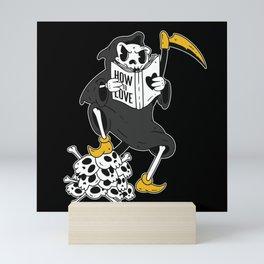 Funny Cartoon Grim Reaper Reading about Love Mini Art Print
