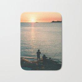 Three fisherman enjoy a beautiful sunset at the shore of 'Colonia del Sacramento, Uruguay'. Bath Mat