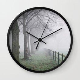 Fence beside an avenue of trees in fog. Norfolk, UK. Wall Clock