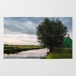Green cottage at summer sunset Rug