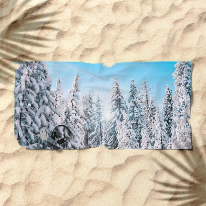 Snow covered evergreens Beach Towel