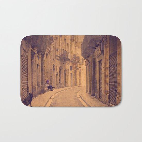 The dog in the narrow street of Barcelona Bath Mat