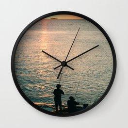 Three fisherman enjoy a beautiful sunset at the shore of 'Colonia del Sacramento, Uruguay'. Wall Clock