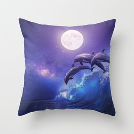 Night ocean with three playful dolphins leaping from sea on surfing wave and full moon shining Throw Pillow