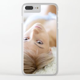 Young girl lying, looking at camera, natural light from window Clear iPhone Case