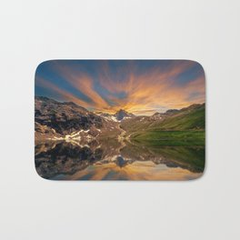 Lake surrounded by mountains cristal clear water with reflection of sky with yellow cloud in the Bath Mat